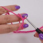 Faden durch ziehen, dabei das Handgelenk etwas nach rechts drehen, so dass der Faden verdreht auf der Nadel liegt.